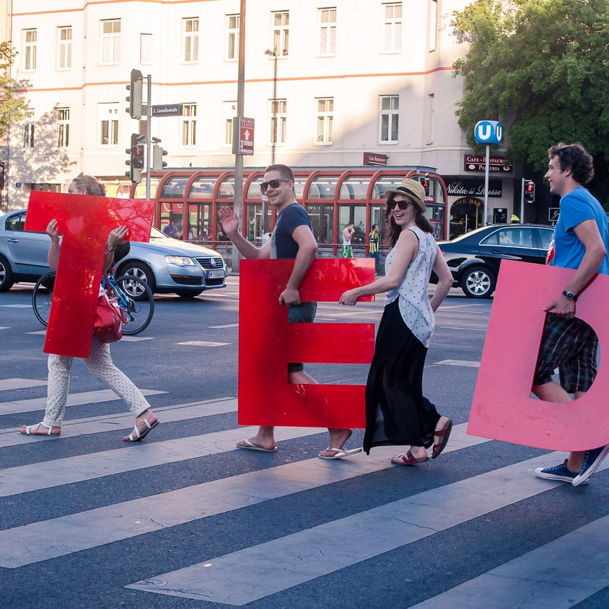 The TEDxDonauinsel Team carrying letters across the street.